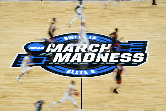 Players run on the court during the first half of a Sweet 16 game between Loyola Chicago and Oregon State in the NCAA men's college basketball tournament at Bankers Life Fieldhouse, Saturday, March 27, 2021, in Indianapolis. (AP Photo/Darron Cummings)