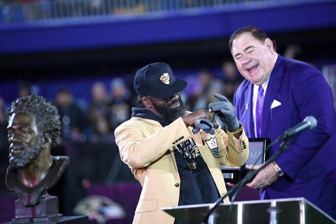 David Baker, right, president of the Pro Football Hall of Fame, looks on as former Baltimore Ravens safety Ed Reed tries on his hall of fame ring presented to him at during a halftime ceremony at an NFL football game between the Baltimore Ravens and the New England Patriots, Sunday, Nov. 3, 2019, in Baltimore. (AP Photo/Nick Wass)