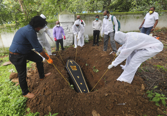 People lower the coffin of a man who died of COVID-19, at a cemetery in Mumbai, India, Tuesday, June 23, 2020. Some Indian states Tuesday were considering fresh lockdown measures to try to halt the spread of the virus in the nation of more than 1.3 billion. (AP Photo/Rafiq Maqbool)