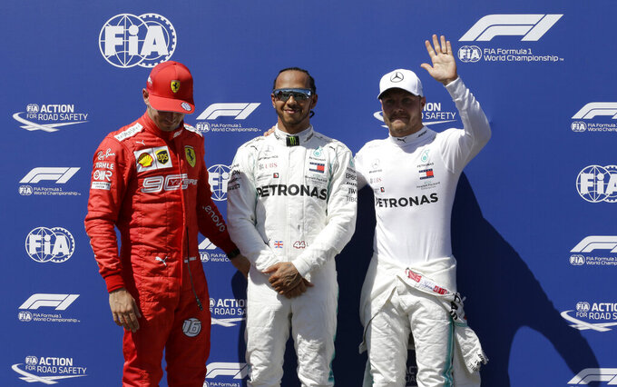 Mercedes driver Lewis Hamilton of Britain, center, who earned pole position, Ferrari driver Charles Leclerc of Monaco, left, who came in third and Mercedes driver Valtteri Bottas of Finland, who earned the second best time, posing for photos after the qualifying session at the Paul Ricard racetrack in Le Castellet, southern France, Saturday, June 22, 2019. The French Formula One Grand Prix will be held on Sunday. (AP Photo/Claude Paris)