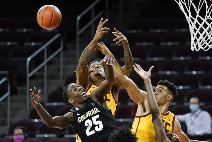 Colorado's McKinley Wright IV, bottom left, is defended by Southern California's Isaiah Mobley, right, and Isaiah White during the second half of an NCAA college basketball game Thursday, Dec. 31, 2020, in Los Angeles. Colorado won 72-62. (AP Photo/Jae C. Hong)