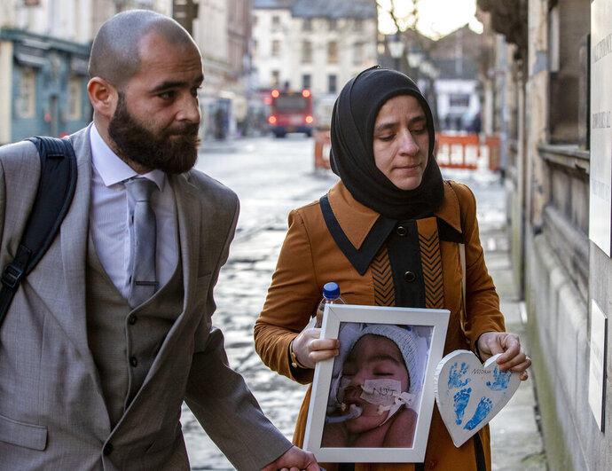 FILE - In this Jan. 20, 2020 file photo, Karwan Ali, left, and Shokhan Namiq, hold a picture of their son, in Preston, England. The parents of a baby who was declared brain dead by doctors has lost the latest round of a legal battle in Britain's courts to keep him on life support. Britain's Court of Appeal on Friday, Feb. 14 rejected an attempt by Karwan Ali and Shokhan Namiq to overturn a High Court order that doctors could stop treating their infant son Midrar Ali. (Peter Byrne/PA via AP)