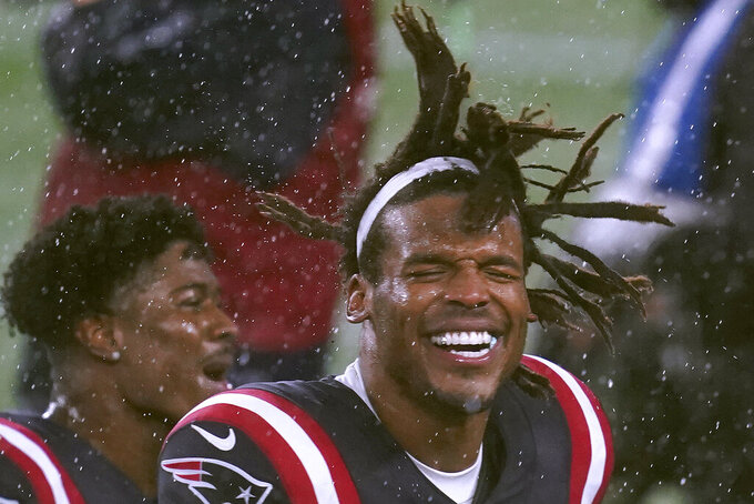 New England Patriots quarterback Cam Newton celebrates in the driving rain after defeating the Baltimore Ravens in an NFL football game, Sunday, Nov. 15, 2020, in Foxborough, Mass. (AP Photo/Elise Amendola)