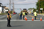 Officials guard a roadblock near a scene where a Baltimore County police officer died, while investigating a suspicious vehicle, Monday, May 21, 2018, in Perry Hall, Md. Heavily armed police swarmed into the leafy suburb, searching for at least one armed suspect. (AP Photo/Patrick Semansky)