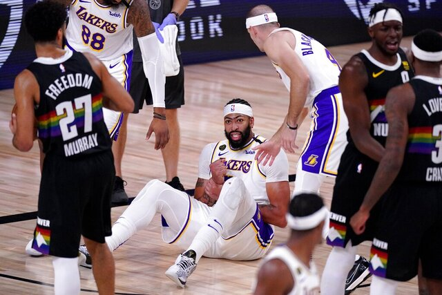 Denver Nuggets' Jamal Murray (27) looks on as Los Angeles Lakers' Anthony Davis (3) grabs his wrist after falling to the floor during play in the second half of Game 3 of the NBA basketball Western Conference final Tuesday, Sept. 22, 2020, in Lake Buena Vista, Fla. (AP Photo/Mark J. Terrill)