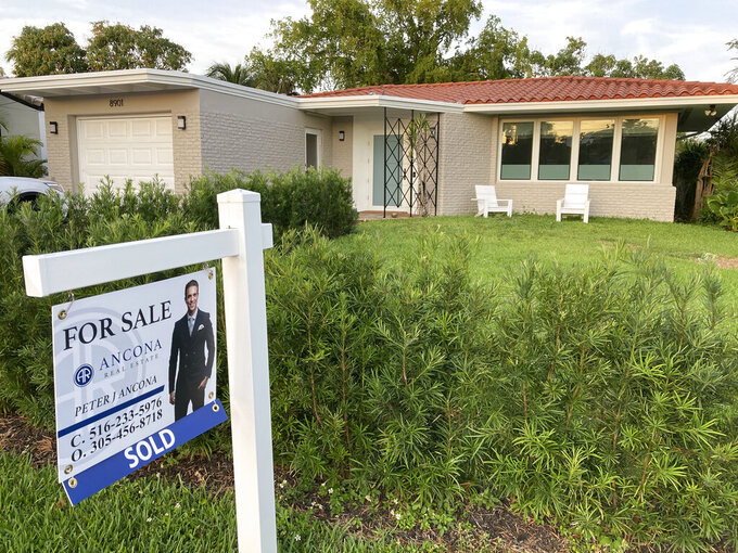 """A home with a """"Sold"""" sign is shown, Sunday, May 2, 2021, in Surfside, Fla.   Mortgage rates rose this week, pushing the benchmark 30-year home loan to the 3% mark for the first time since mid-April. Signs continued of the economy's recovery from the pandemic recession and a burst of inflation rattled stock markets.   (AP Photo/Wilfredo Lee)"""