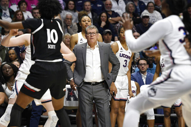 FILE- In this March 9, 2020, file photo, Connecticut head coach Geno Auriemma, center, watches play at the end of an NCAA college basketball game against Cincinnati in the American Athletic Conference tournament finals at Mohegan Sun Arena, Monday, in Uncasville, Conn. Auriemma and UConn are back home in the Big East sitting in a familiar spot — atop the preseason poll. The Huskies, who returned to the conference after seven years in the American, were the unanimous choice to win the league the Big East announced Thursday, Ocrt. 29, 2020. (AP Photo/Jessica Hill, File)