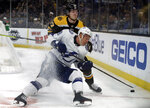Boston Bruins defenseman Torey Krug (47) and Tampa Bay Lightning left wing Ondrej Palat (18) compete for the puck during the first period of an NHL hockey game Thursday, Feb. 28, 2019, in Boston. (AP Photo/Elise Amendola)