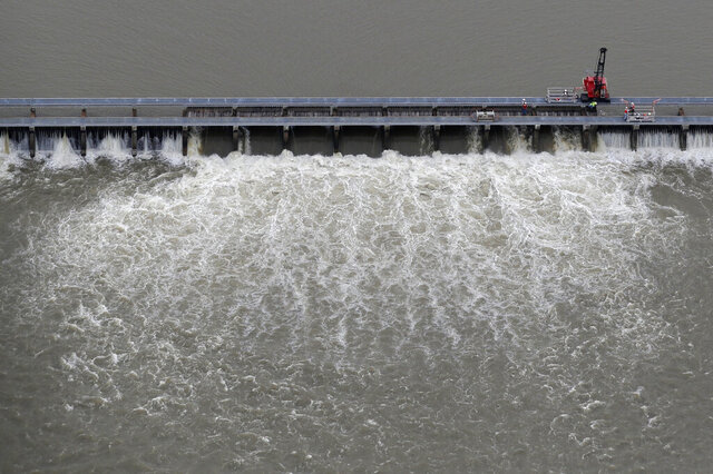 FILE - In this May 10, 2019 file photo, workers open bays of the Bonnet Carre Spillway, to divert rising water from the Mississippi River to Lake Pontchartrain, upriver from New Orleans, in Norco, La. The major flood control structure on the Mississippi River may have to soon be opened up to ease pressure on New Orleans levees, federal authorities said Tuesday, March 31, 2020. The river is expected to crest above 17 feet (5.2 meters) at a key New Orleans gauge as early as Friday, April 3, 2020, the U.S. Army Corps of Engineers said in a news release.  That would likely lead to the opening of a structure that diverts water through the Bonnet Carré Spillway. (AP Photo/Gerald Herbert, File)