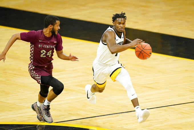 Iowa guard Joe Toussaint drives up court ahead of North Carolina Central guard Nicolas Fennell, left, during the first half of an NCAA college basketball game, Wednesday, Nov. 25, 2020, in Iowa City, Iowa. (AP Photo/Charlie Neibergall)