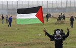A masked protester waves his national flag near the fence of the Gaza Strip border with Israel, marking first anniversary of Gaza border protests east of Gaza City, Saturday, March 30, 2019.  Tens of thousands of Palestinians gathered Saturday at rallying points near the Israeli border to mark the first anniversary of weekly protests in the Gaza Strip, as Israeli troops fired tear gas and opened fire at small crowds of activists who approached the border fence. (AP Photo/Adel Hana)