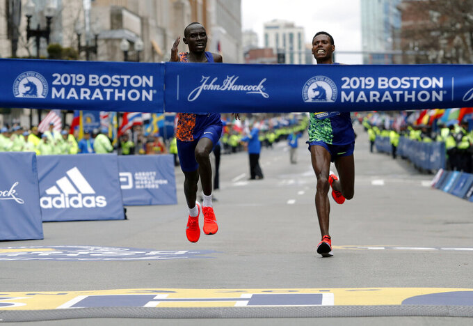 FILE - In this April 15, 2019, file photo, Lawrence Cherono, left, of Kenya, runs to the finish line to win the 123rd Boston Marathon in front of Lelisa Desisa, of Ethiopia, right, in Boston. The Boston Marathon is offering refunds for the first time because of the new coronavirus pandemic. Race organizers say anyone who was entered in the 124th edition of the race this month can still run on the rescheduled date, Sept. 14. But if they can't make it, they can have their money back. (AP Photo/Winslow Townson, File)