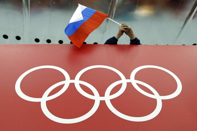 FILE - In this Feb. 18, 2014 file photo, a Russian skating fan holds the country's national flag over the Olympic rings before the men's 10,000-meter speedskating race at Adler Arena Skating Center during the Winter Olympics in Sochi, Russia. A person familiar with the case tells The Associated Press that Russia's anti-doping agency could face suspension again based on information indicating data from the Moscow drug-testing lab had been manipulated before being delivered to the World Anti-Doping Agency earlier this year. (AP Photo/David J. Phillip, File)