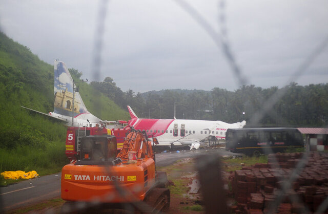 The Air India Express flight that skidded off a runway while landing at the airport in Kozhikode, Kerala state, India, Saturday, Aug. 8, 2020. The special evacuation flight bringing people home to India who had been trapped abroad because of the coronavirus skidded off the runway and split in two while landing in heavy rain killing more than a dozen people and injuring dozens more. (AP Photo/C.K.Thanseer)