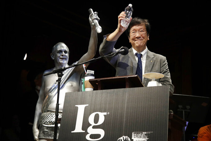 FILE - In this Sept. 12, 2019 file photo, Shigeru Watanabe, of Japan, receives the Ig Nobel award in chemistry for estimating the total saliva volume produced per day by a typical five-year-old, at the 29th annual Ig Nobel awards ceremony at Harvard University, in Cambridge, Mass. The spoof prizes for weird and sometimes head-scratching scientific achievement will be presented online in 2021 due to the coronavirus pandemic. (AP Photo/Elise Amendola, File)