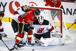 New Jersey Devils goalie Mackenzie Blackwood, right, blocks the net on Calgary Flames' Derek Ryan, center, as Devils' Will Butcher watches during the second period of an NHL hockey game Thursday, Nov. 7, 2019, in Calgary, Alberta. (Jeff McIntosh/The Canadian Press via AP)
