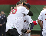 Former Boston Red Sox pitcher Curt Schilling, left, hugs Dustin Pedroia during a ceremony before the home opener baseball game between the the Red Sox and Toronto Blue Jays, Tuesday, April 9, 2019, in Boston. (AP Photo/Charles Krupa)