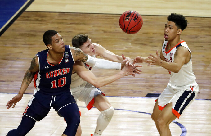 Auburn's Samir Doughty (10), Virginia's Kyle Guy and Kihei Clark (0) battle for a loose ball during the first half in the semifinals of the Final Four NCAA college basketball tournament, Saturday, April 6, 2019, in Minneapolis. (AP Photo/Matt York)