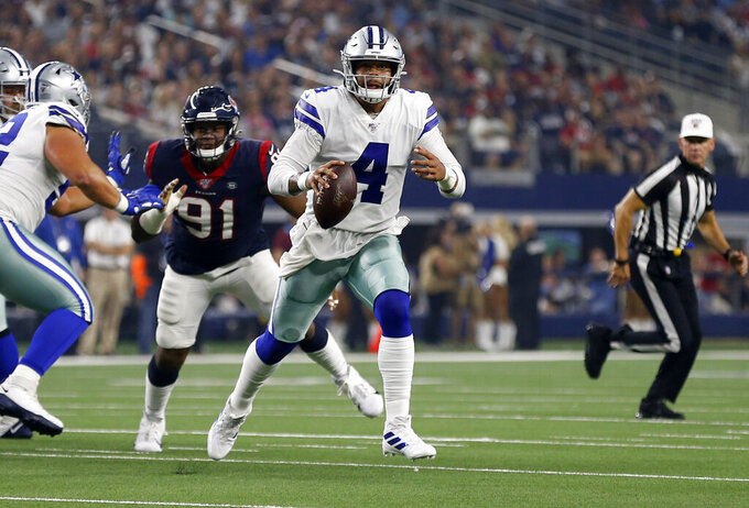 Dallas Cowboys quarterback Dak Prescott (4) scrambles out of the pocket under pressure from Houston Texans' Carlos Watkins (91) in the first half of a preseason NFL football game in Arlington, Texas, Saturday, Aug. 24, 2019. (AP Photo/Ron Jenkins)