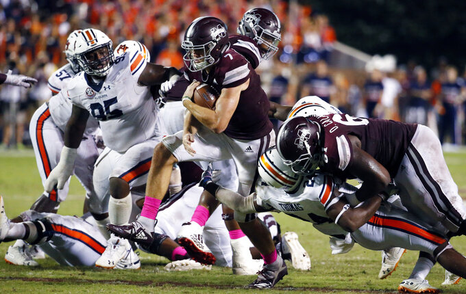 Mississippi State quarterback Nick Fitzgerald (7) runs past Auburn defenders for a 27-yard touchdown during the second half of their NCAA college football game in Starkville, Miss., Saturday, Oct. 6, 2018. Mississippi State won 23-9. (AP Photo/Rogelio V. Solis)