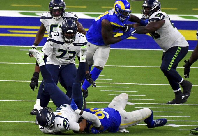 Defensive end Michael Brockers #90 of the Los Angeles Rams sacks quarterback Russell Wilson #3 of the Seattle Seahawks in the fourth quarter of a NFL football game at SoFi Stadium in Inglewood on Sunday, November 15, 2020. Los Angeles Rams won 23-16. (Keith Birmingham/The Orange County Register via AP)