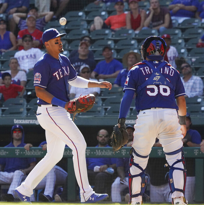 A pop up drops between Texas Rangers first baseman Ronald Guzman, left, and catcher Jose Trevino (56) during the ninth inning of a baseball game against the Boston Red Sox on Thursday, Sept. 26, 2019, in Arlington, Texas. (AP Photo/Louis DeLuca)