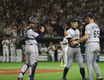 Seattle Mariners right fielder Ichiro Suzuki, second from right, is applauded by teammates Brandon Brennan (65), catcher Omar Narvaez and the Oakland Athletics, rear, while leaving the field for defensive substitution in the eighth inning of Game 2 of their Major League baseball opening series at Tokyo Dome in Tokyo, Thursday, March 21, 2019. (AP Photo/Toru Takahashi)
