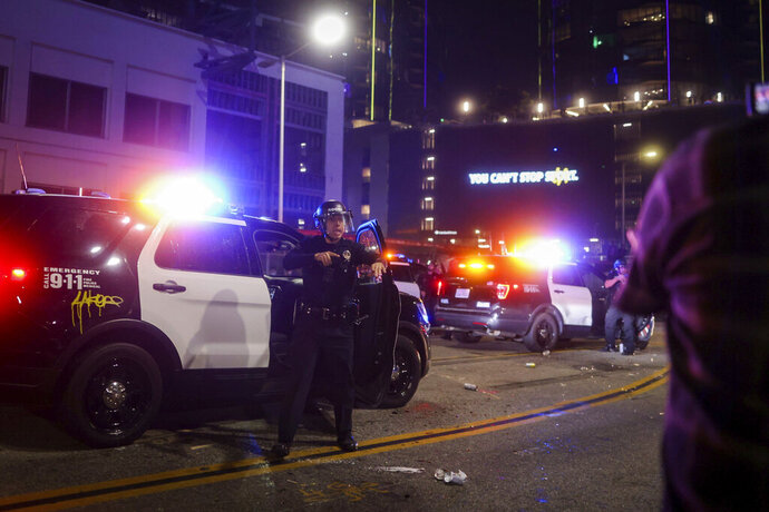 Los Angeles Police officers try to disperse rowdy fans outside of Staples Center, Sunday, Oct. 11, 2020, in Los Angeles, after the Lakers defeated the Miami Heat in Game 6 of basketball's NBA Finals to win the championship. (AP Photo/Christian Monterrosa)