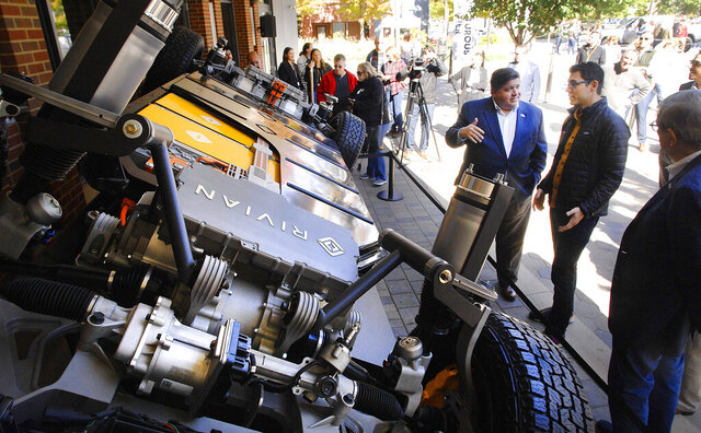 FILE - In this Oct. 13, 2019, file photo, Illinois Gov. J.B. Pritzker, left, talks with RJ Scaringe, CEO of Rivian Automotive, about the company's innovative electric vehicle chassis called a