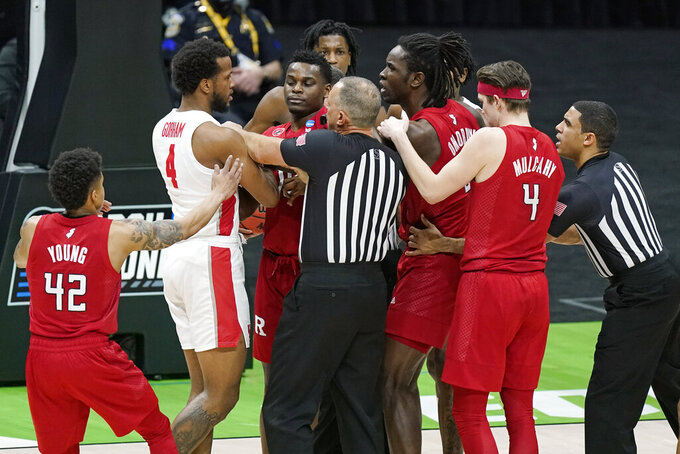 Officials separate Rutgers and Houston players during the first half of a college basketball game in the second round of the NCAA tournament at Lucas Oil Stadium in Indianapolis Sunday, March 21, 2021. (AP Photo/Mark Humphrey)