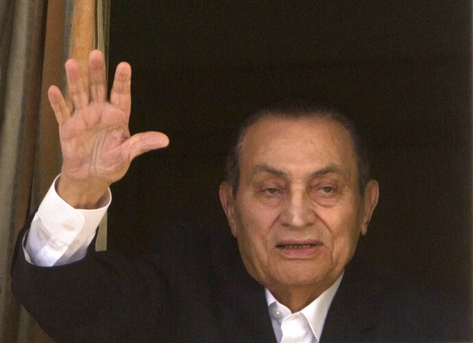 "FILE - In this April 25, 2016 file photo, ousted Egyptian President Hosni Mubarak waves to his supporters from his room at the Maadi Military Hospital, where he is hospitalized, in Cairo, Egypt.  Egypt's former autocratic ruler Hosni Mubarak, who was forced to step down following 2011 mass protests, has undergone a surgery, his eldest son tweeted on Friday, Jan. 24, 2020. Alaa Mubarak tweeted that his 91-year-old father was operated on Thursday and that his condition was ""stable"".  He did not provide any further details about the surgery. (AP Photo/Amr Nabil, File)"