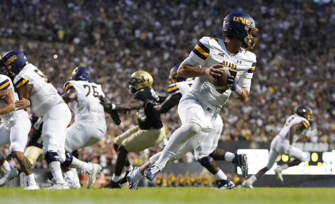 Northern Colorado quarterback Dylan McCaffrey, front right, rolls out to pass the ball against Colorado in the first half of an NCAA college football game Friday, Sept. 3, 2021, in Boulder, Colo. (AP Photo/David Zalubowski)