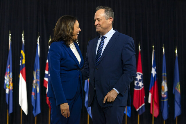 Democratic presidential candidate former Vice President Joe Biden's running mate Sen. Kamala Harris, D-Calif., and her husband Douglas Emhoff look to each other at the end of a campaign event at Alexis Dupont High School in Wilmington, Del., Wednesday, Aug. 12, 2020. (AP Photo/Carolyn Kaster)