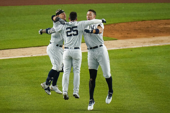 New York Yankees' Gleyber Torres (25) celebrates with Rougned Odor, left, and Aaron Judge, right, after hitting an RBI-single during the ninth inning of a baseball game against the Chicago White Sox, Friday, May 21, 2021, in New York. (AP Photo/Frank Franklin II)
