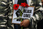 FILE - In this June 7, 2020, file photo, a protester holds a placard in front of the U.S. embassy, during the Black Lives Matter protest rally in London, in response to the recent killing of George Floyd by police officers in Minneapolis, that has led to protests in many countries and across the U.S. Black Lives Matter has gone mainstream — and black activists are carefully assessing how they should respond. (AP Photo/Frank Augstein, File)