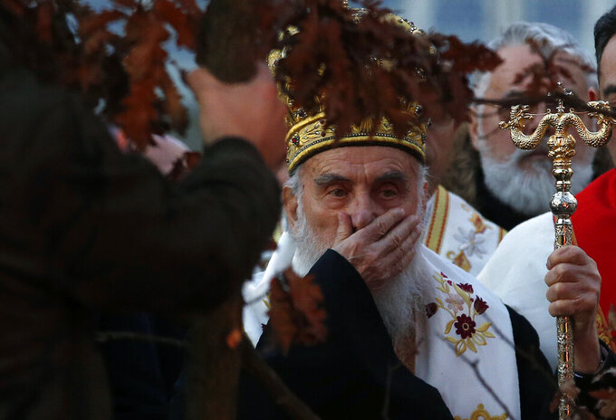 FILE - In this Jan. 6, 2020. file photo, Serbian Patriarch Irinej gestures during a ceremonial burning of dried oak branches, in front of St. Sava church in Belgrade, Serbia. The Serbian Orthodox Church says Patriarch Irinej has been hospitalized after testing positive for the new coronavirus. Patriarch Irinej last Sunday led the prayers at the big public funeral for the church head in Montenegro, Bishop Amfilohije, who had died after contracting the virus. (AP Photo/Darko Vojinovic, File)