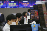 A currency trader wearing a mask watches monitors at the foreign exchange dealing room of the KEB Hana Bank headquarters in Seoul, South Korea, Tuesday, Jan. 28, 2020. Asian shares continued to fall Tuesday, dragged down by worries about an outbreak of a new virus in China that threatens global economic growth. (AP Photo/Ahn Young-joon)