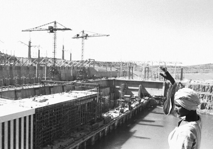 FILE - In this Feb. 27, 1968 file photo, an Egyptian worker waves as he stands on top of a rock overlooking the partly constructed power station on the Aswan High Dam, Egypt. Egyptians are marking 50 years since the inauguration of the Nile dam, a massive feat of construction that has shaped the course of modern-day Egypt. It spared it from seasonal droughts and flooding, and generated electricity. (AP Photo, File)