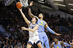 Villanova's Collin Gillespie, left, goes up for a shot past Marquette's Theo John during the second half of an NCAA college basketball game Wednesday, Feb. 12, 2020, in Villanova, Pa. (AP Photo/Matt Slocum)