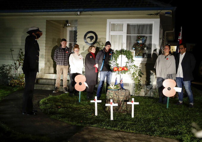 """Neighbors gather at dawn to commemorate Anzac Day in a suburb of Christchurch, New Zealand, Saturday, April 25, 2020. Many New Zealanders participated in the """"Stand At Dawn"""" initiative to commemorate Anzac Day after the traditional services were canceled due to COVID-19. (AP Photo/Mark Baker)"""