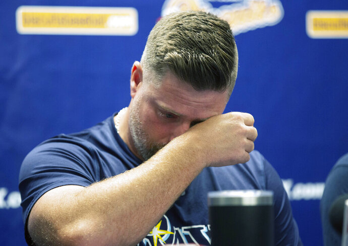 Montgomery Biscuits manager Morgan Ensberg wipes away tears during a news conference about pitcher Blake Bivens' wife and child who were killed in a triple homicide, Thursday, Aug. 29, 2019 in Montgomery, Ala.  A Virginia man appears to have used a .30-30 rifle and a sledgehammer in a deadly rampage that claimed the lives of minor league baseball player Blake Biven's wife, 1-year-old son and mother-in-law, according to court documents released Thursday. (Kirsten Fiscus/Montgomery Advertiser via AP)