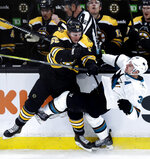 Boston Bruins center Noel Acciari, left, drops San Jose Sharks center Logan Couture, right, to the ice with a hard check during the first period of an NHL hockey game in Boston, Tuesday, Feb. 26, 2019. (AP Photo/Charles Krupa)