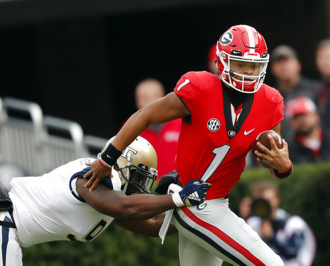 FILE - In this Saturday, Nov. 24, 2018, file photo, Georgia quarterback Justin Fields (1) tries to escape from Georgia Tech linebacker Victor Alexander (9) in the second half of an NCAA college football game in Athens, Ga. With the college football season set to start for most teams this weekend, the NCAA has been handing down rulings left and right in waiver cases involving transfers seeking immediate eligibility. (AP Photo/John Bazemore, File)