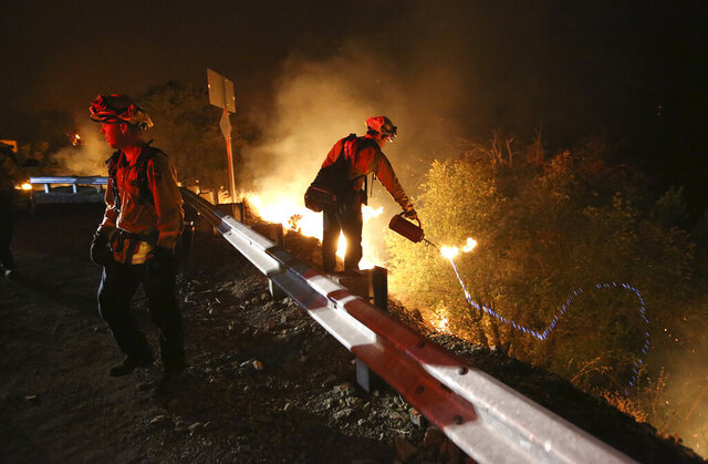 California Department of Forestry and Fire Protection firefighters initiate a fire to deprive the advancing Jones Fire of fuel, early Tuesday, Aug. 18, 2020, along Highway 49 near Grass Valley, Calif. (Elias Funez/The Union via AP)