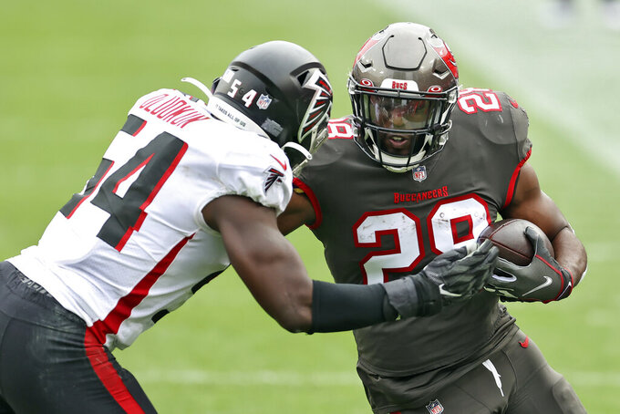 FILE - In this  Sunday, Jan. 3, 2021 file photo, Atlanta Falcons linebacker Foye Oluokun (54) stops Tampa Bay Buccaneers running back Leonard Fournette (28) during the first half of an NFL football game in Tampa, Fla. Leonard Fournette and Kansas City Chiefs Le'Veon Bell  go from losing squads to Super Bowl. (AP Photo/Mark LoMoglio, File)