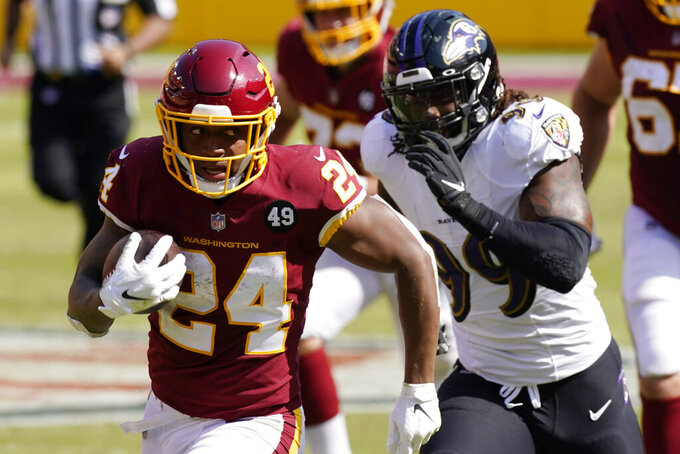 Washington Football Team running back Antonio Gibson (24) is chased by Baltimore Ravens outside linebacker Matt Judon (99) during the first half of an NFL football game Sunday, Oct. 4, 2020, in Landover, Md. (AP Photo/Steve Helber)
