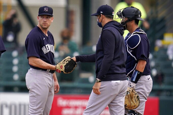 New York Yankees manager Aaron Boone, center, takes the ball from pitcher Trevor Lane, left, with catcher Kyle Higashioka watching during a fourth-inning pitching change in a spring training exhibition baseball game against the Pittsburgh Pirates at LECOM Park in Bradenton, Fla., Saturday, March 6, 2021. (AP Photo/Gene J. Puskar)