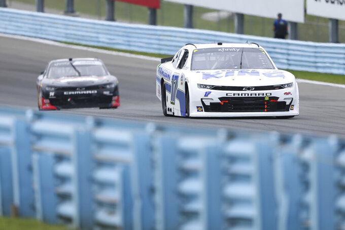 Josh Bilicki, right, drives through the Esses in the NASCAR Xfinity Series auto race at Watkins Glen International in Watkins Glen, N.Y., on Saturday, Aug. 7, 2021. (AP Photo/Joshua Bessex)