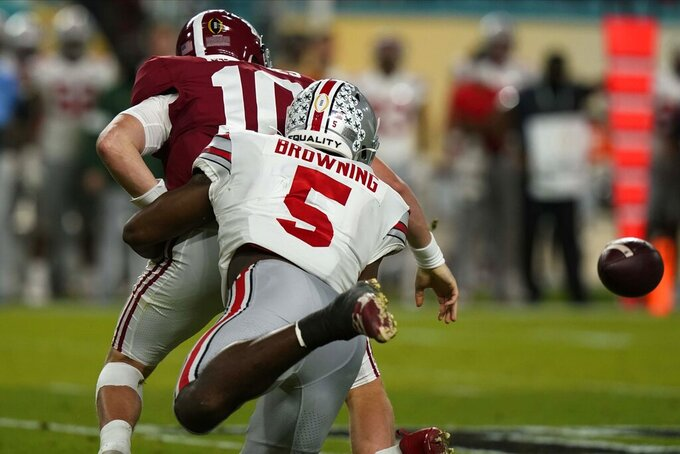 Ohio State linebacker Baron Browning forces a fumble by Alabama quarterback Mac Jones during the first half of an NCAA College Football Playoff national championship game, Monday, Jan. 11, 2021, in Miami Gardens, Fla. (AP Photo/Lynne Sladky)