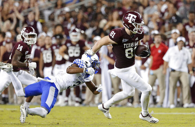 Texas A&M tight end Jace Sternberger (81) breaks a tackle-attempt by Kentucky safety Jordan Griffin (3) as wide receiver Camron Buckley (14) looks on after Sternberger caught the pass intended for Buckley that he ran in for a touchdown during the second half of an NCAA college football game Saturday, Oct. 6, 2018, in College Station, Texas. (AP Photo/Michael Wyke)